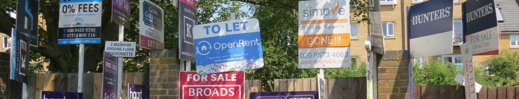 Estate agent boards showing homes to let and houses for sale